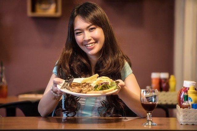 dívka s talířem v ruce se usmívá